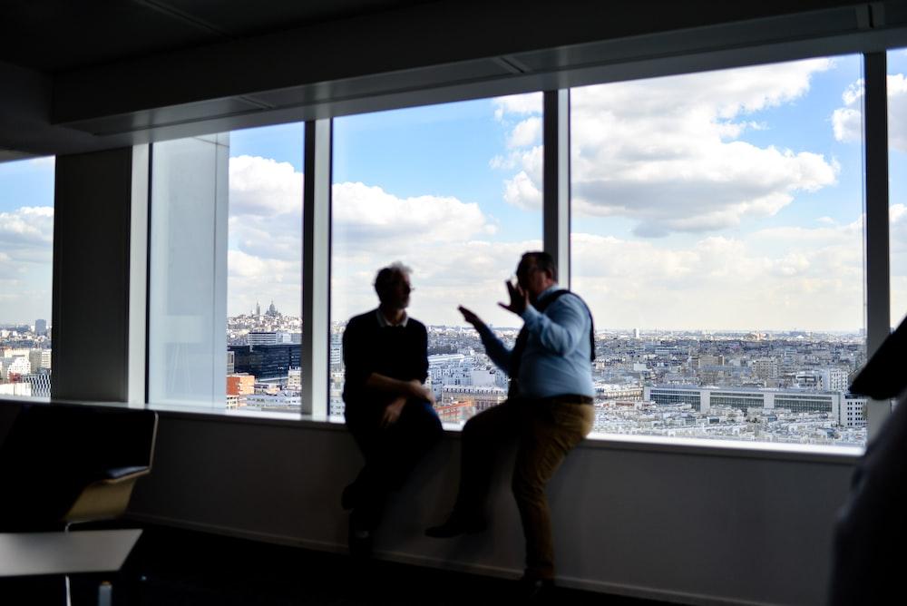 two men sitting beside window having conversation