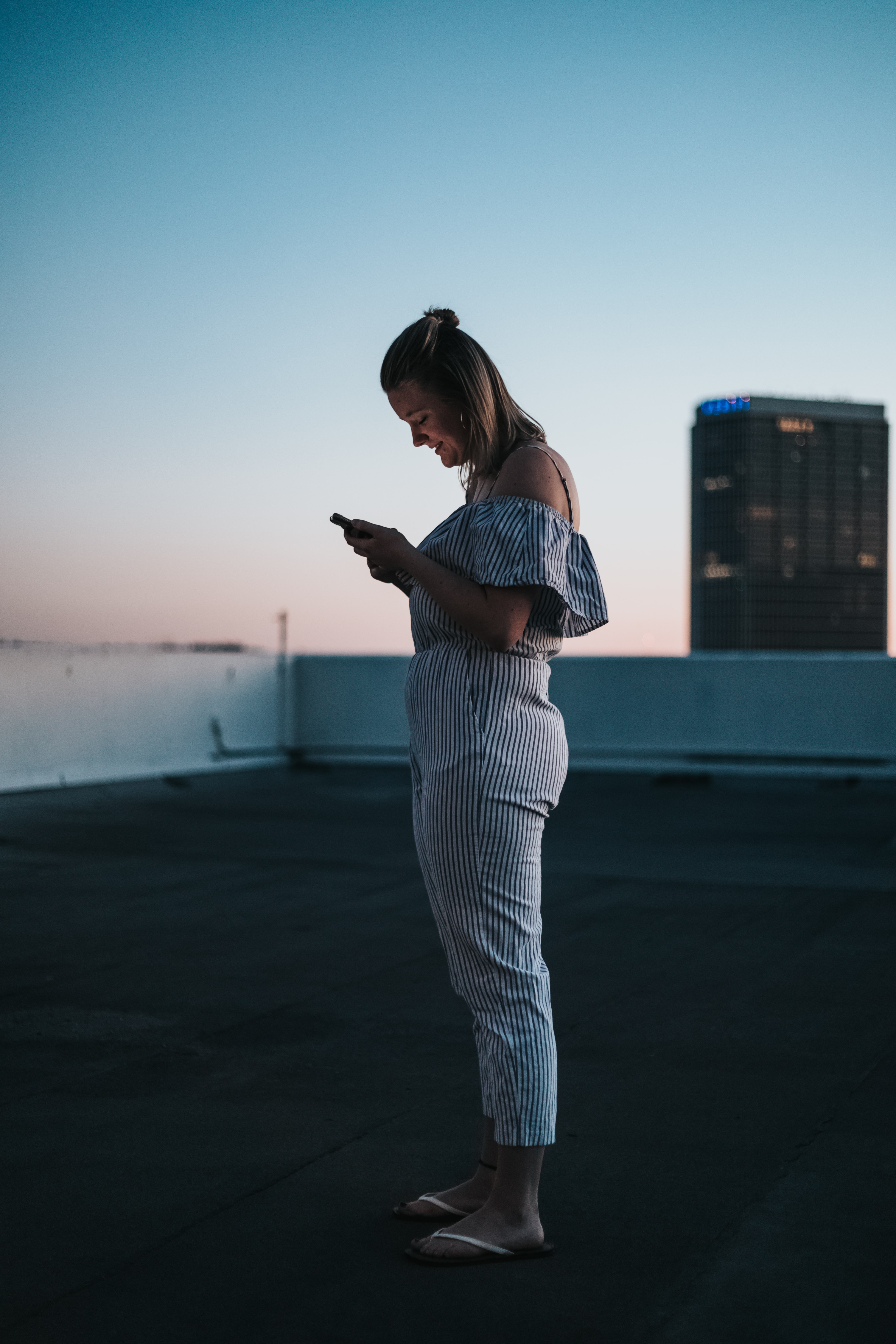 woman standing on rooftop smiling white using smartphone