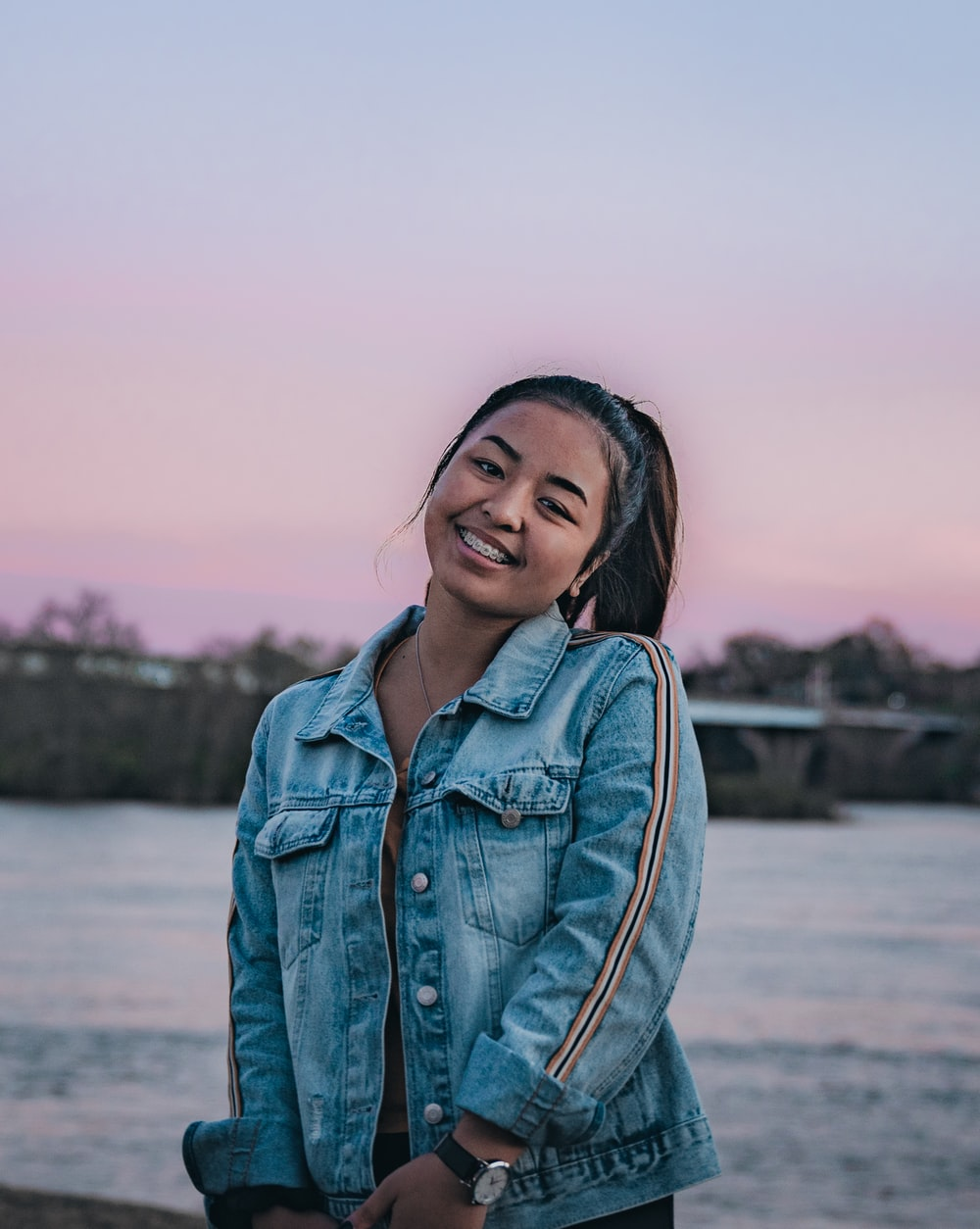 smiling woman in blue denim jacket by body of water