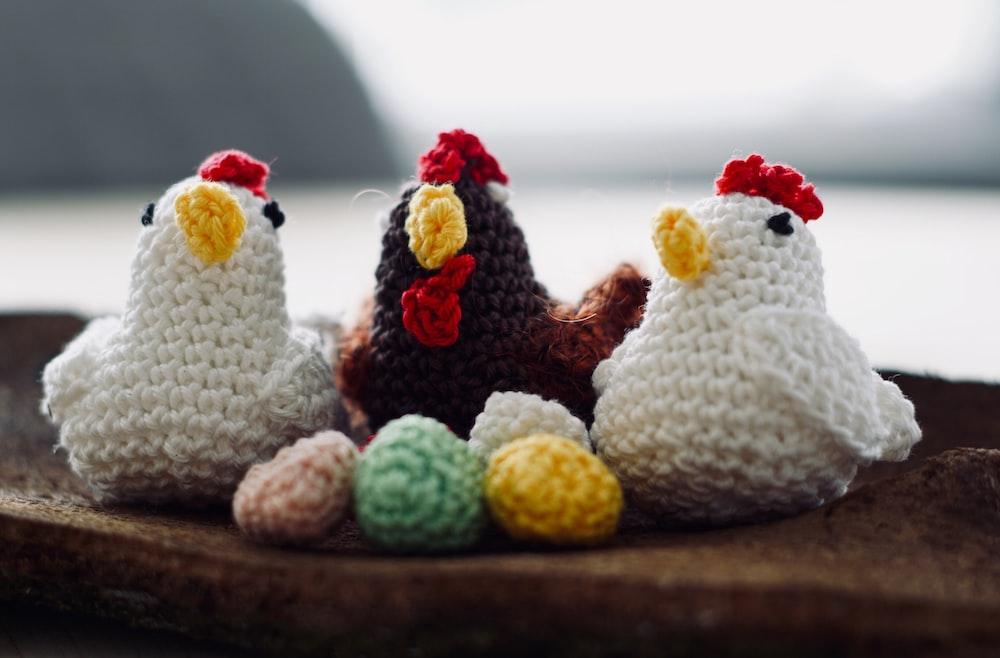 three knit chicken figures on brown wood