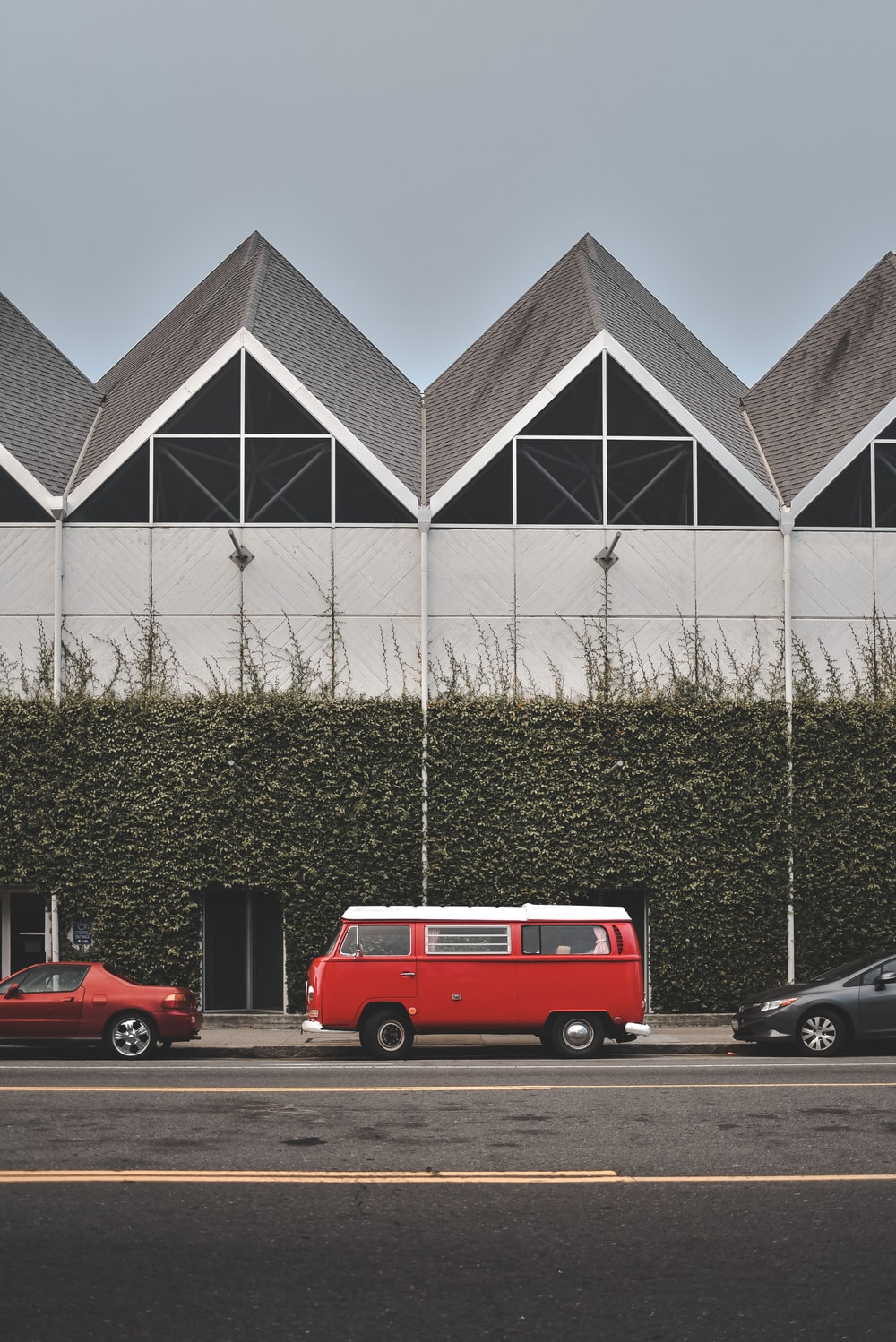red and white Volkswagen van parked infront of vine covered wall