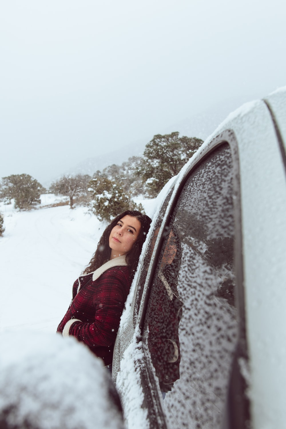 woman in red and white jacket leaning on car during winter season
