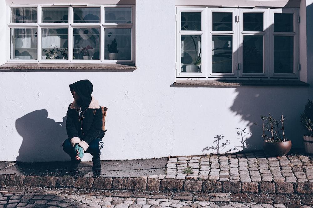 woman squatting near white wall