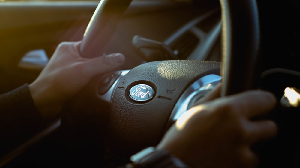 person holding Ford steering wheel