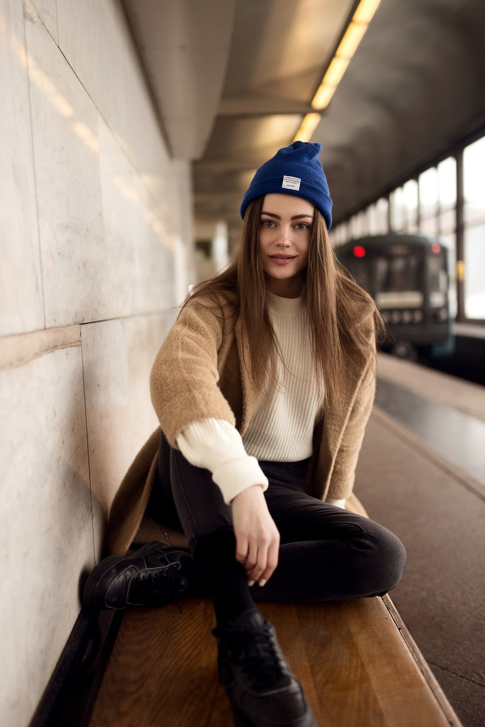 woman wearing beige sweater and black pants sitting on bench