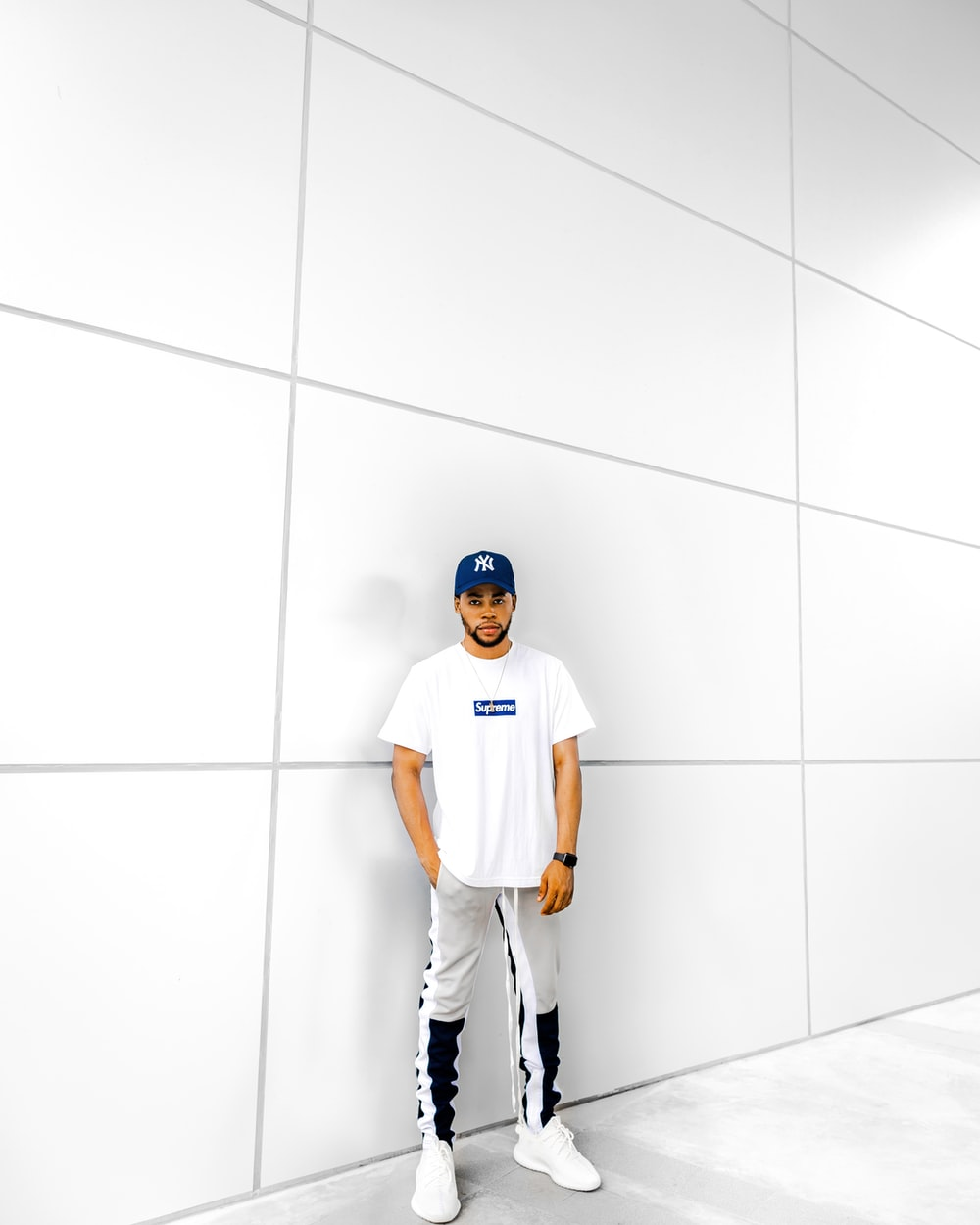 man wearing white crew-neck t-shirt and grey pants and fitted cap