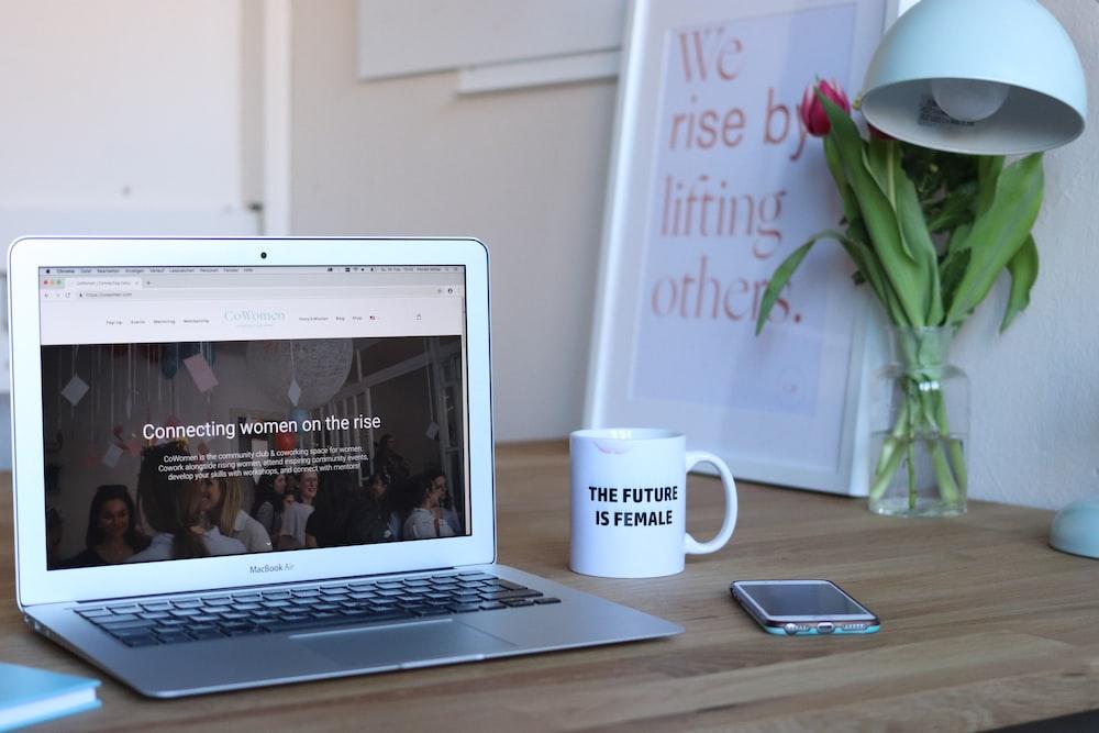 MacBook Air beside cup