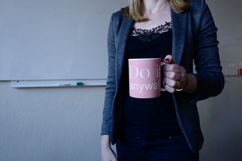 woman in gray blazer holding pink and white ceramic coffee mug