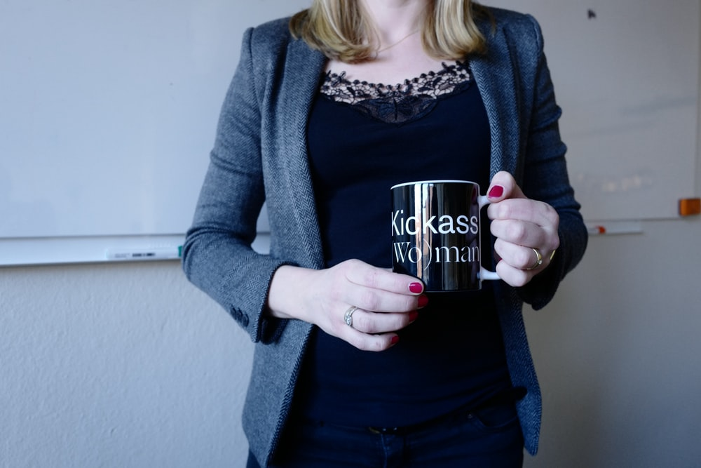 woman wearing blue cardigan holding black mug