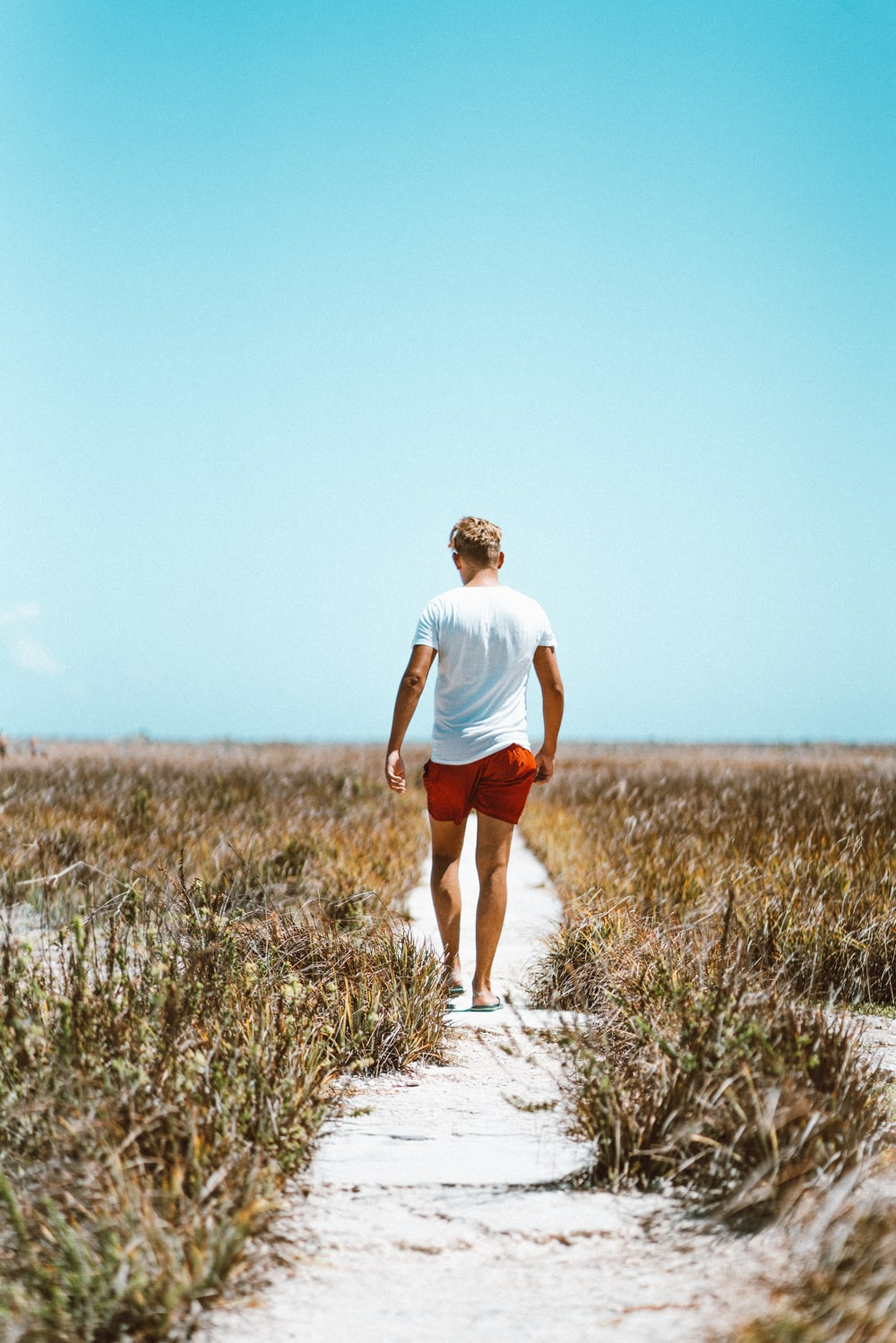 man in white shirt and red shorts walking on white sand between grasses