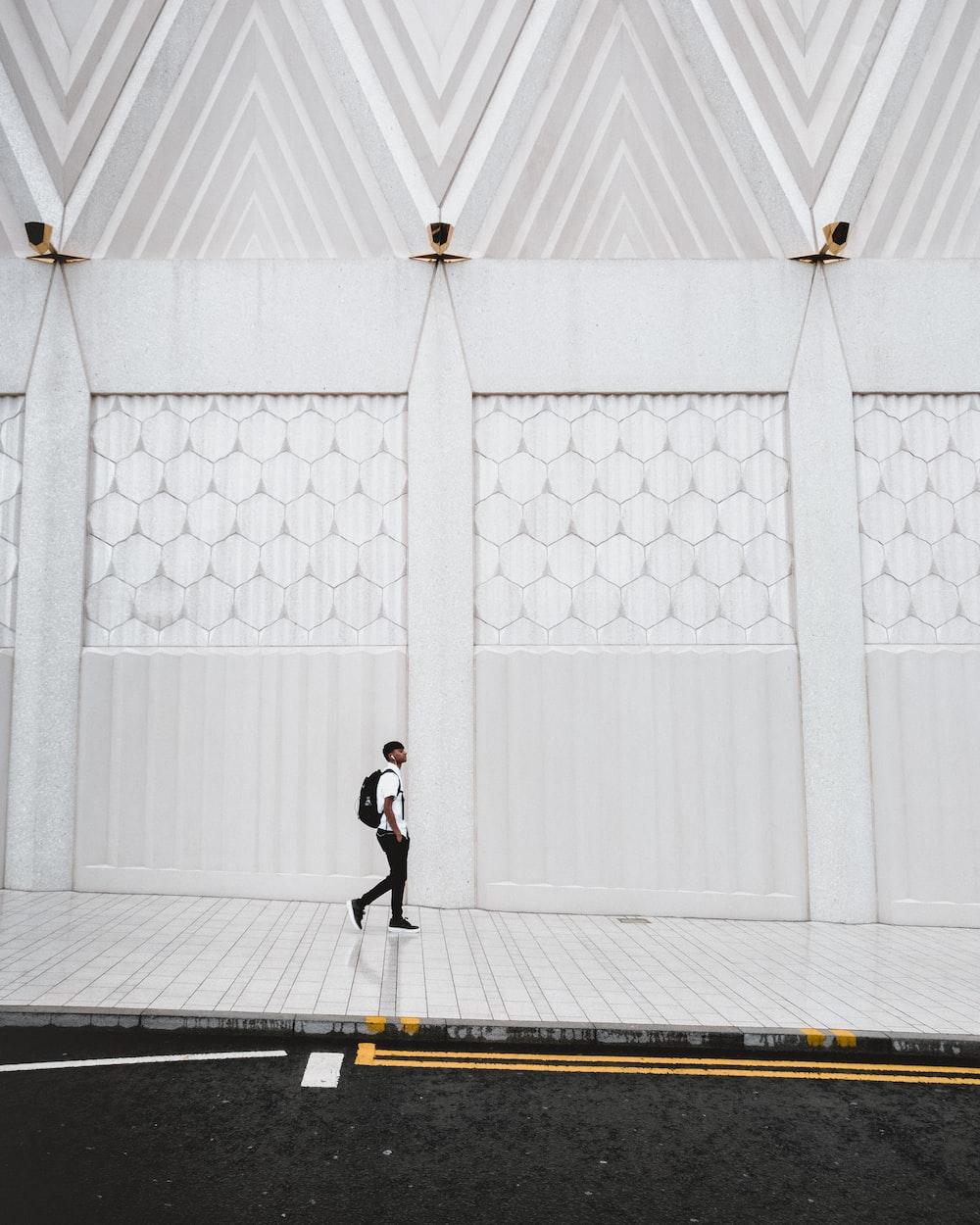 man walking on white concrete pavement
