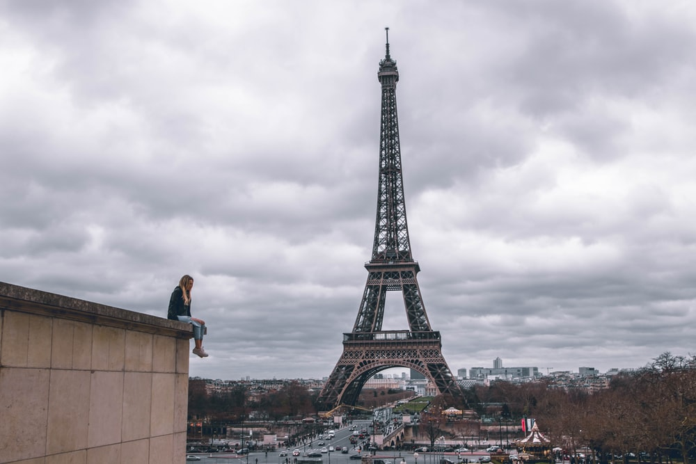 man sitting on the building watching the Eiffel Tower