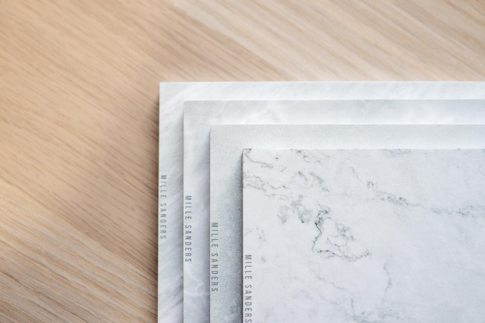 four white ceramic tiles on brown wooden surface