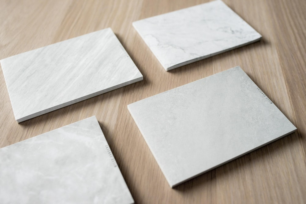four white tiles on wooden surface