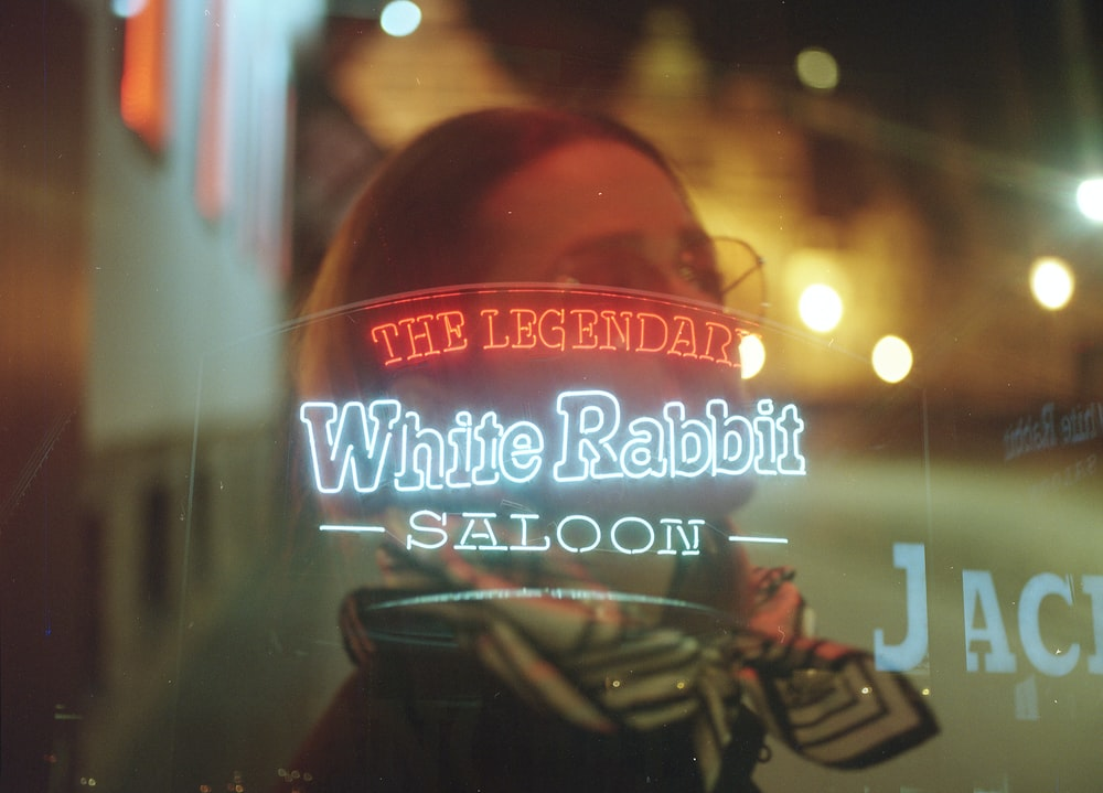 reflection of White Rabbit Saloon signage from glass wall