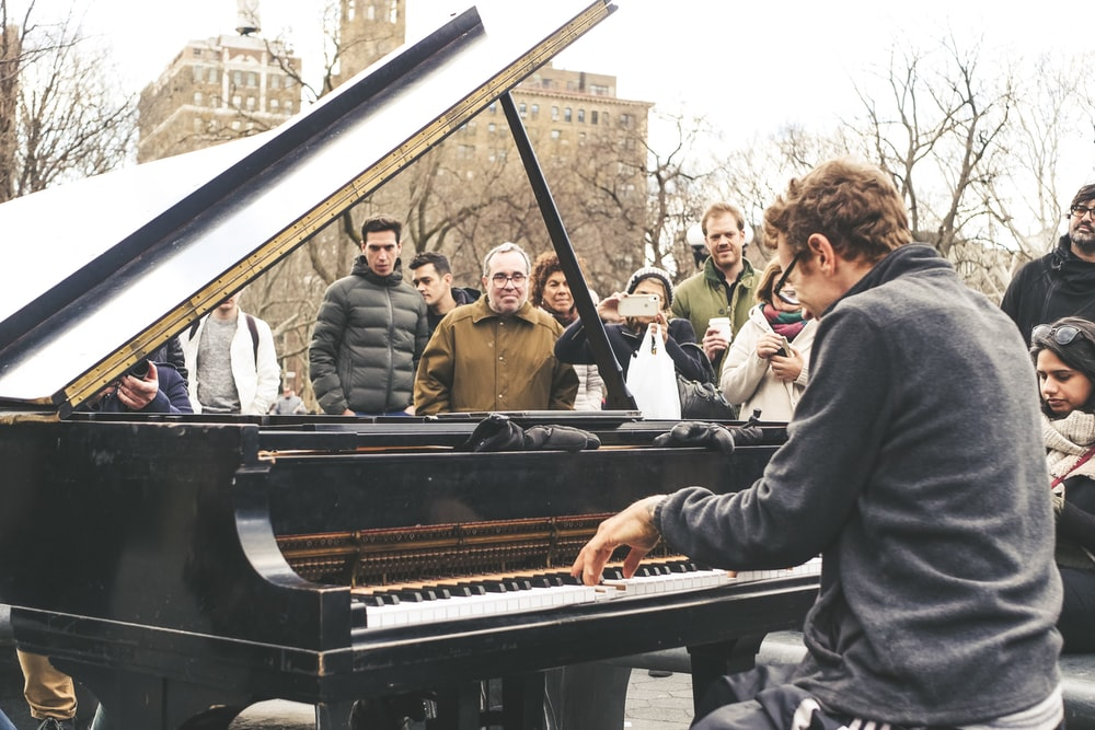 man playing piano in public place