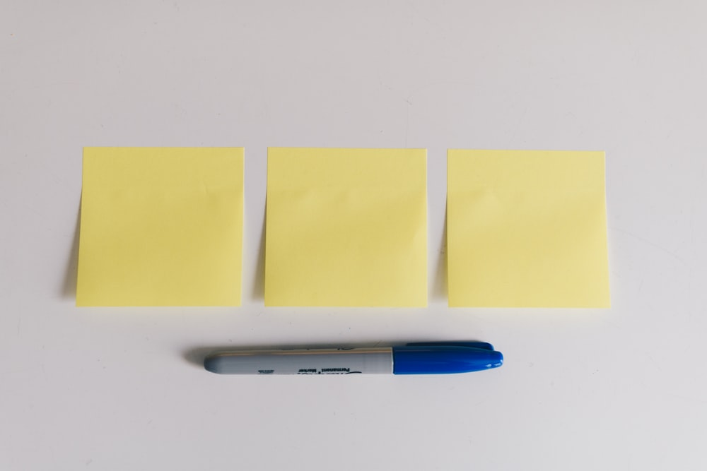 blue sharpie beside yellow sticky notes