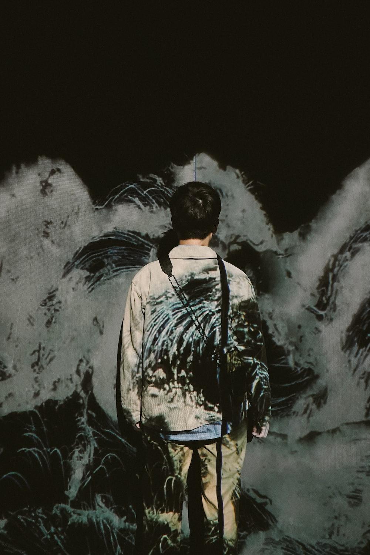 man facing wall with graffiti painting
