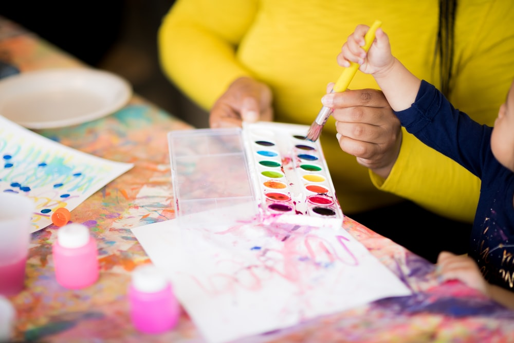 toddler holding paintbrush standing beside woman holding water paint
