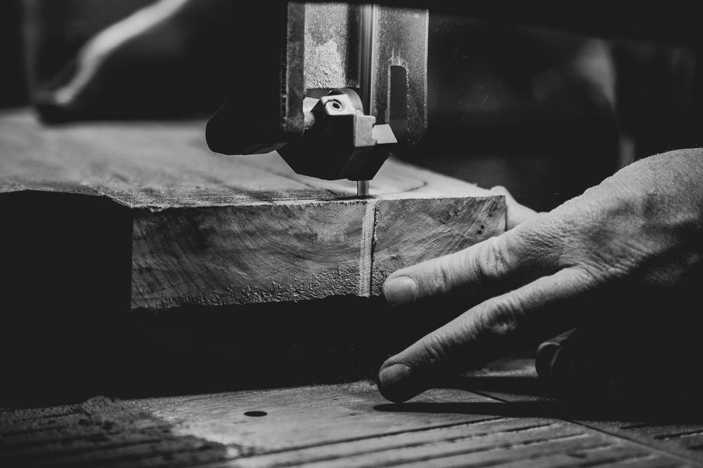 grayscale photography of person cutting slab