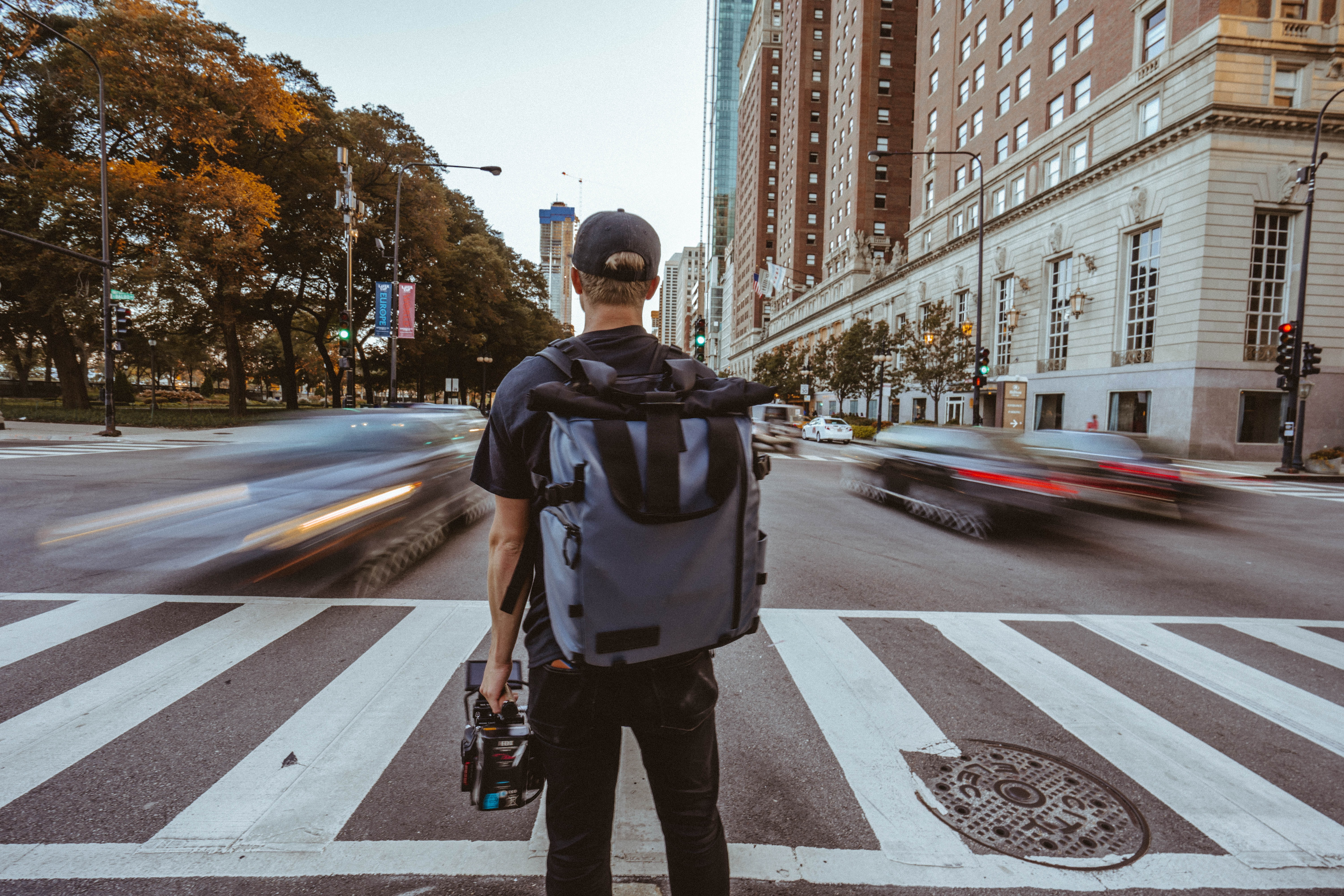 man with backpack standing near pedestrian lane