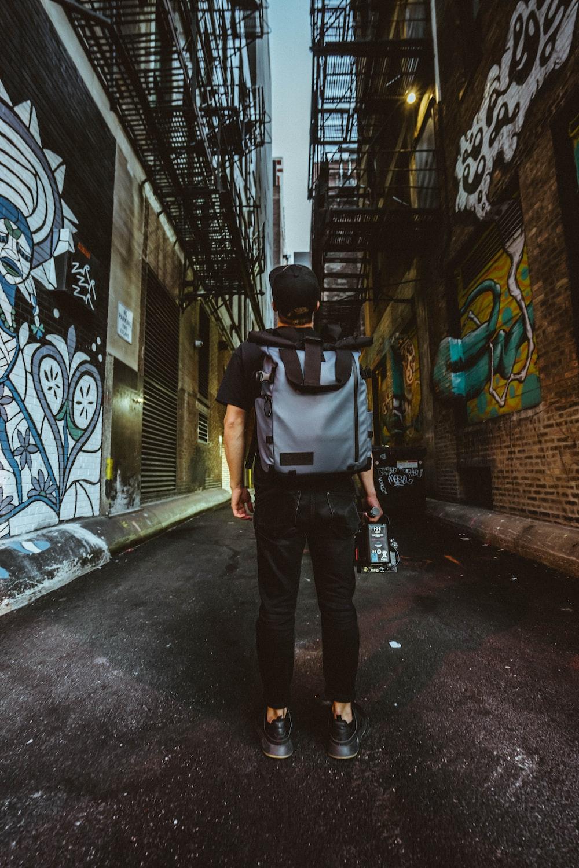 man in black and white backpack walking on sidewalk during daytime