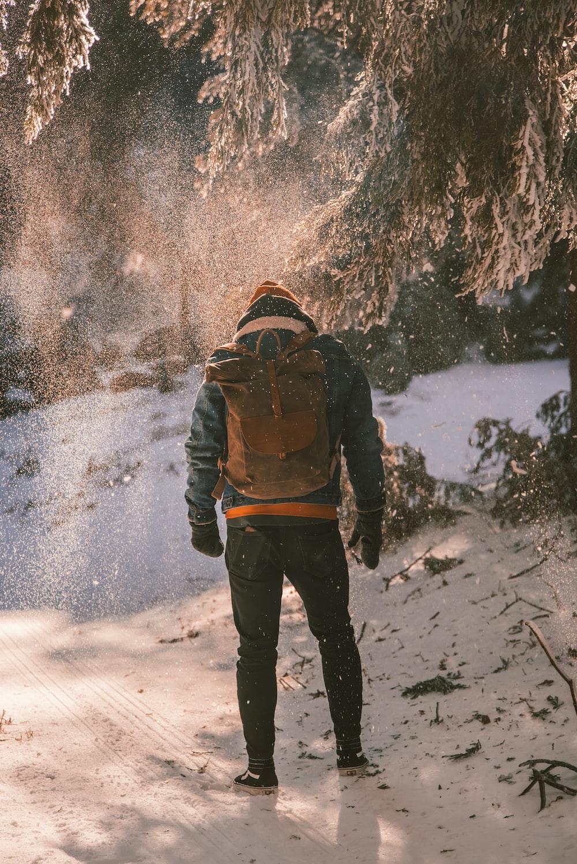 man walking along snowy mountain