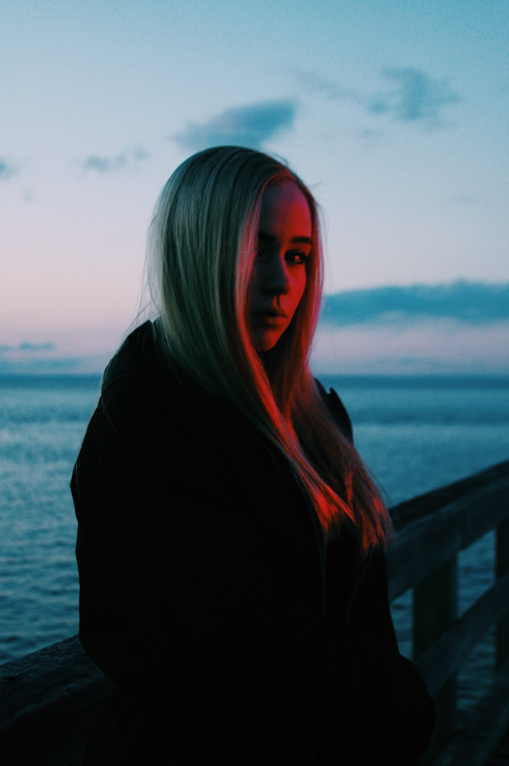 woman wearing black jacket standing across body of water