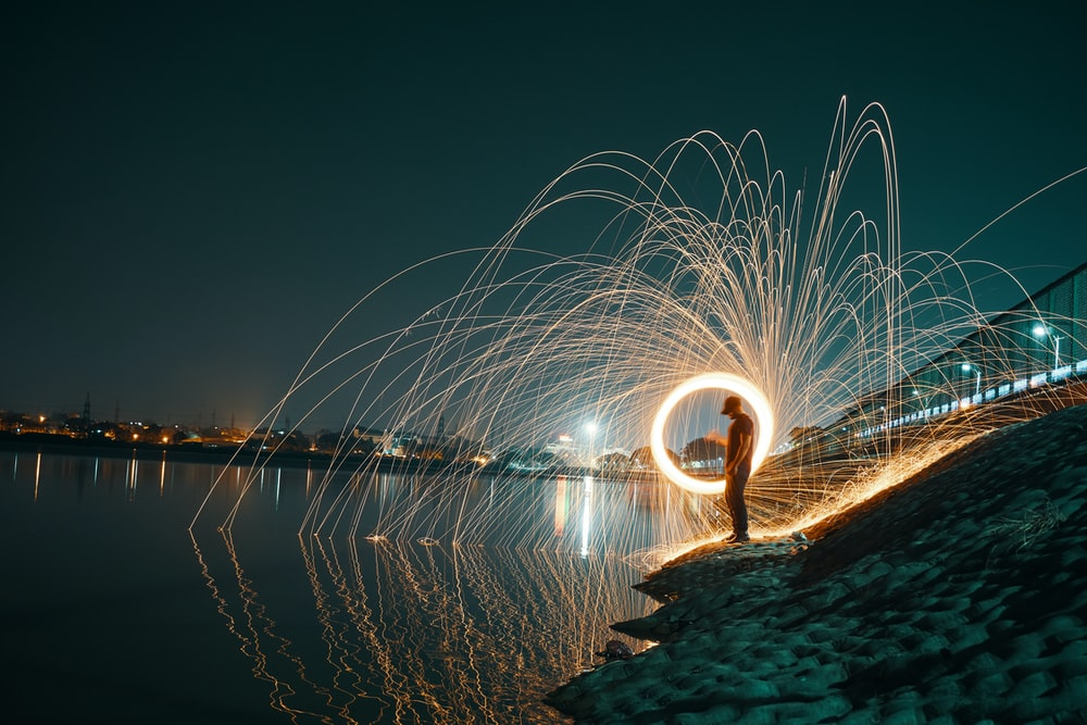 time lapse photography of man spinning lighted steel wool near body of water
