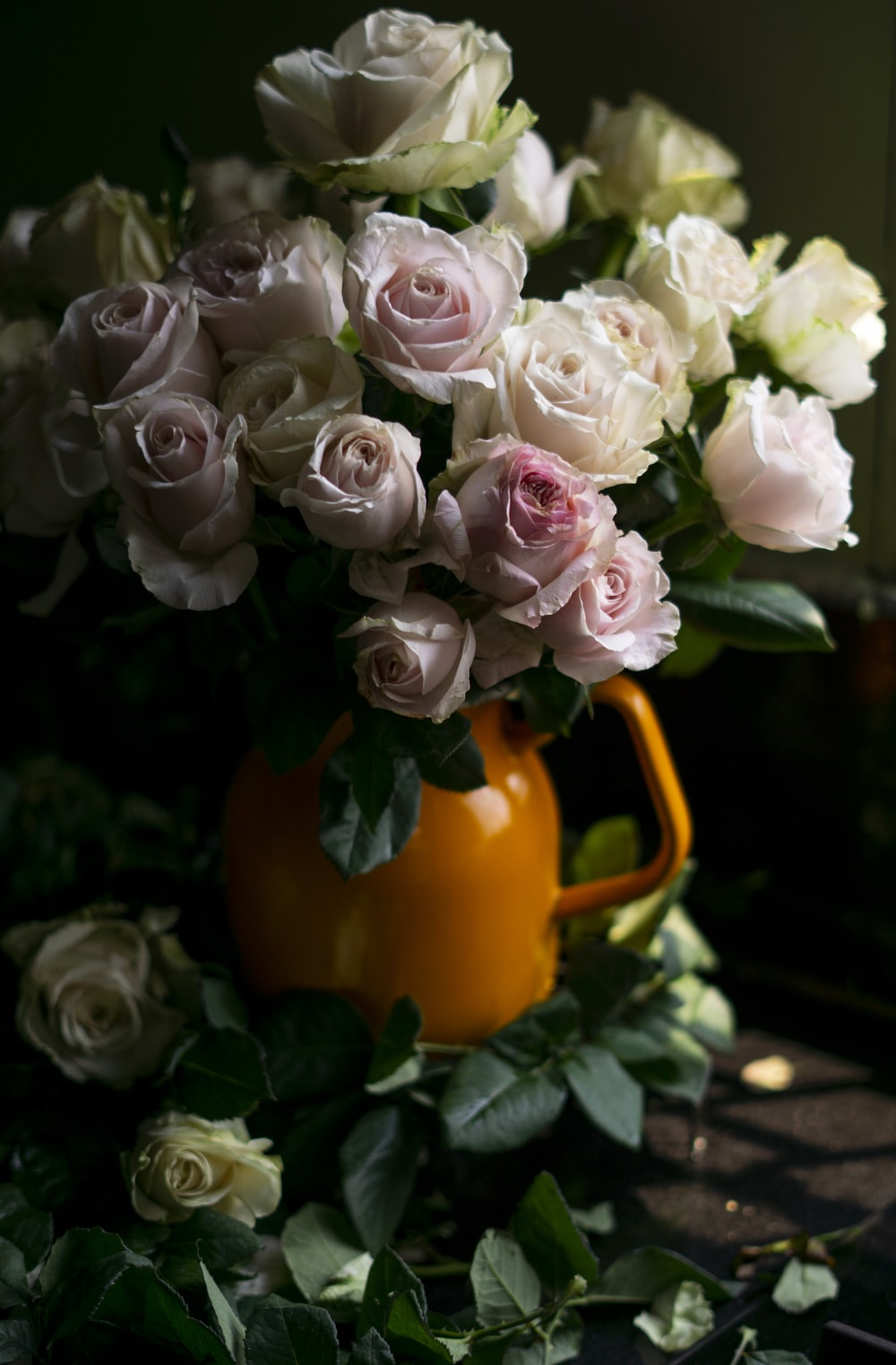 a bouquet of white and pink flowers on an orange pot