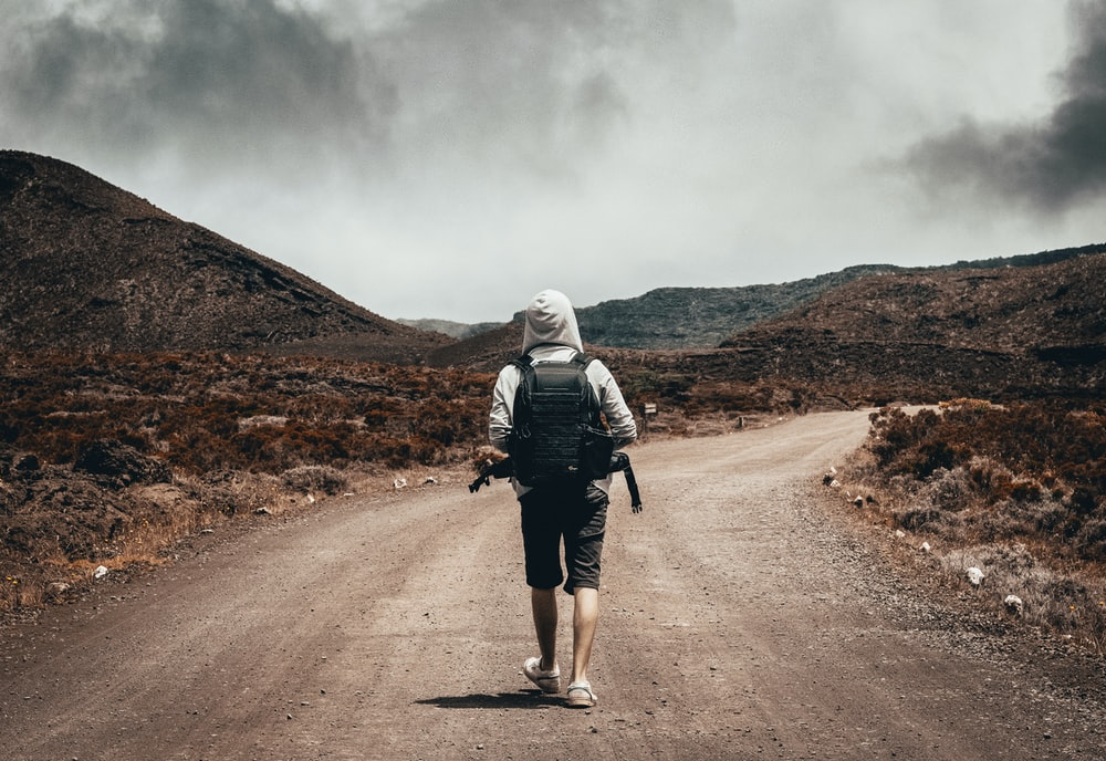 man in gray hoodie carrying backpack walking under the sun