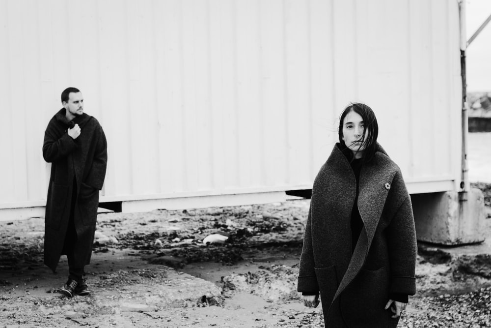 grayscale photography of woman and man standing wearing coat
