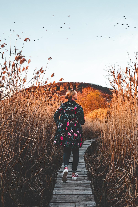 woman standing between brown bushes