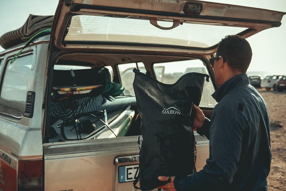 man loading black bag in back of suv
