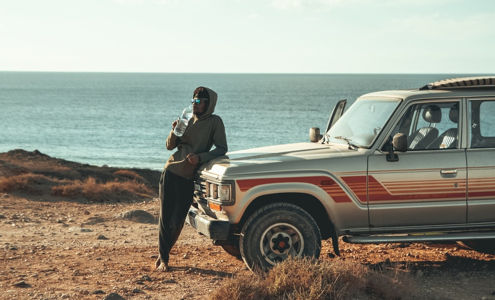 man leaning in front of SUV