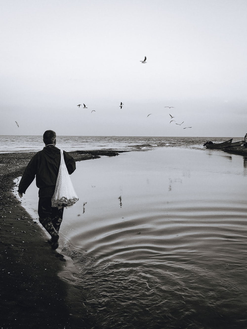 grayscale photography of man carrying plastic pack on back walking on water