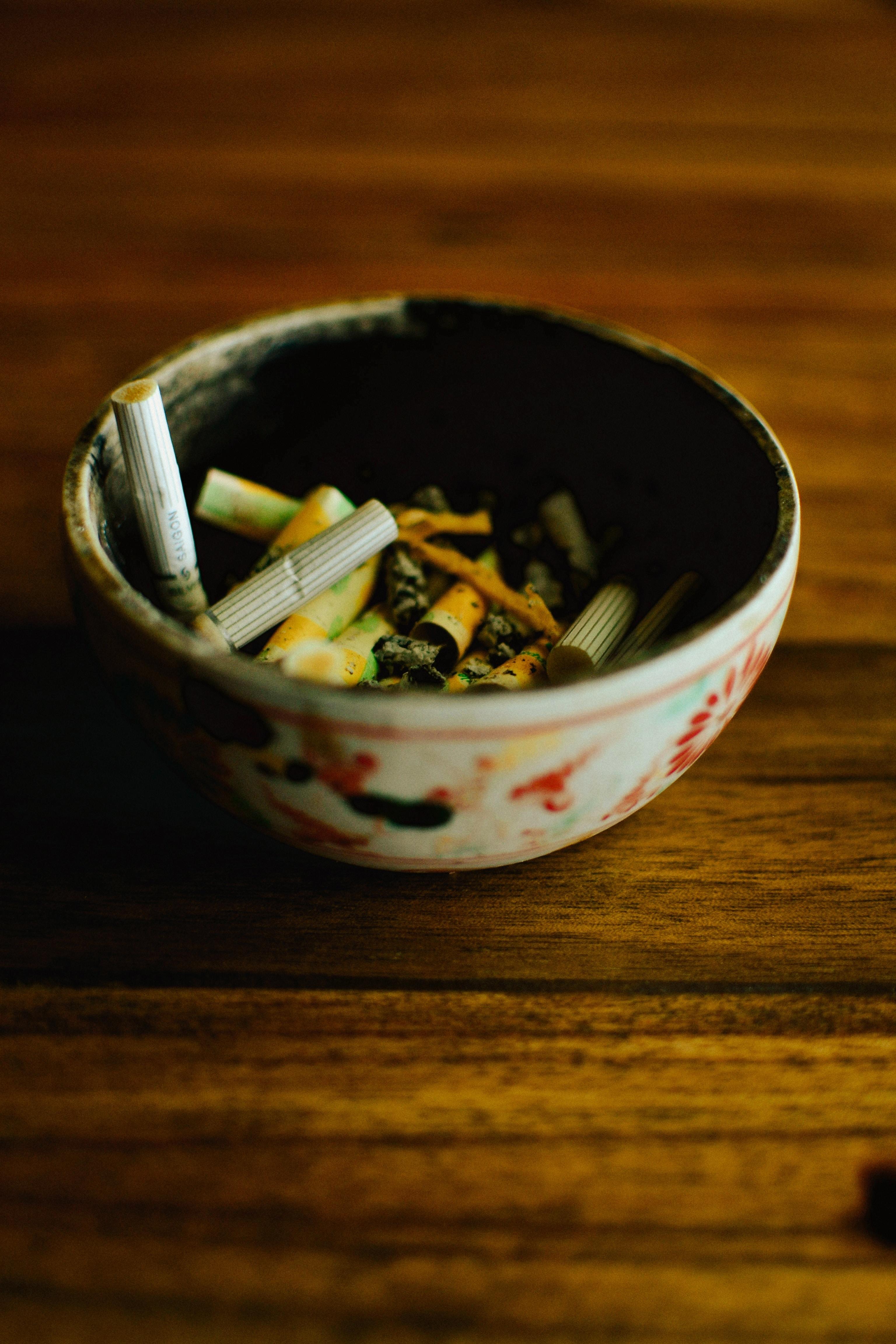 cigarette butts in white ashtray