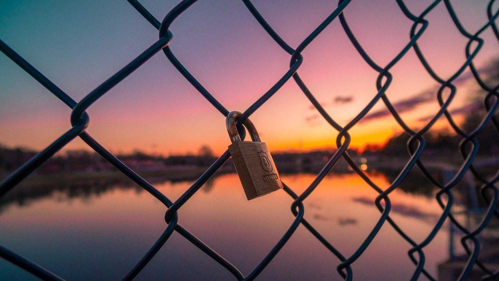 closeup photo of gray padlock locked on gray mesh fence
