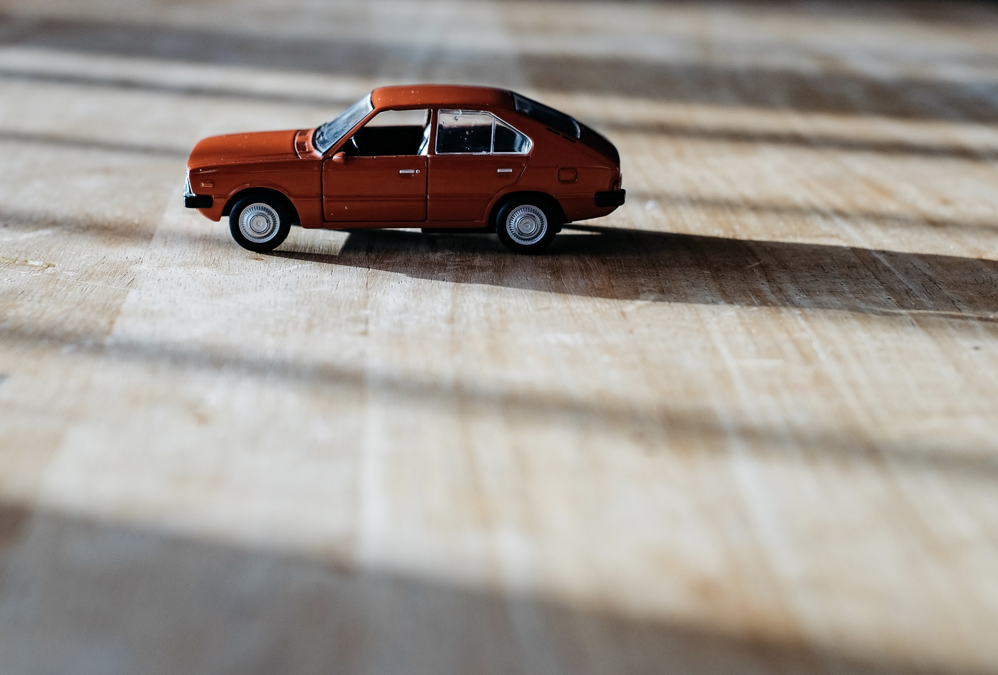 red 5-door hatchback vehicle scale model on top of brown surface