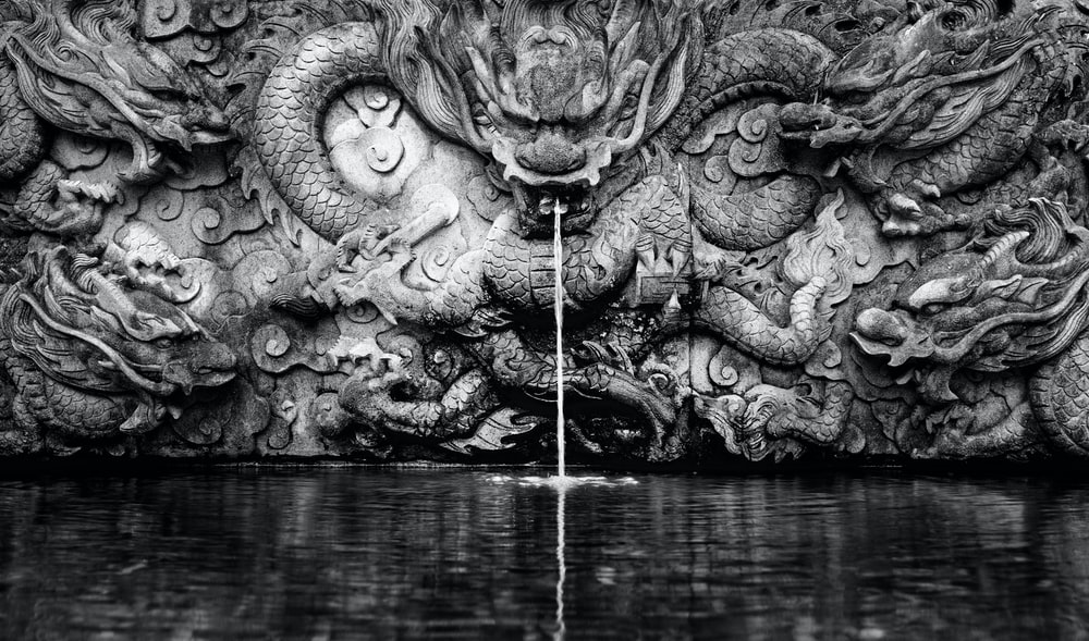 grayscale photography of dragon water fountain