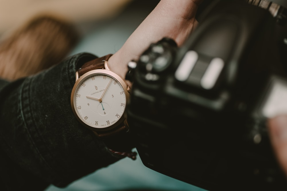 round white and gold-colored analog watch at 10:05
