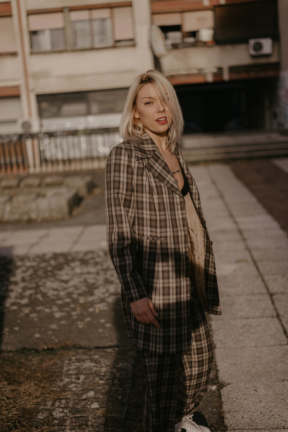 woman wearing brown and white plaid coat during daytime