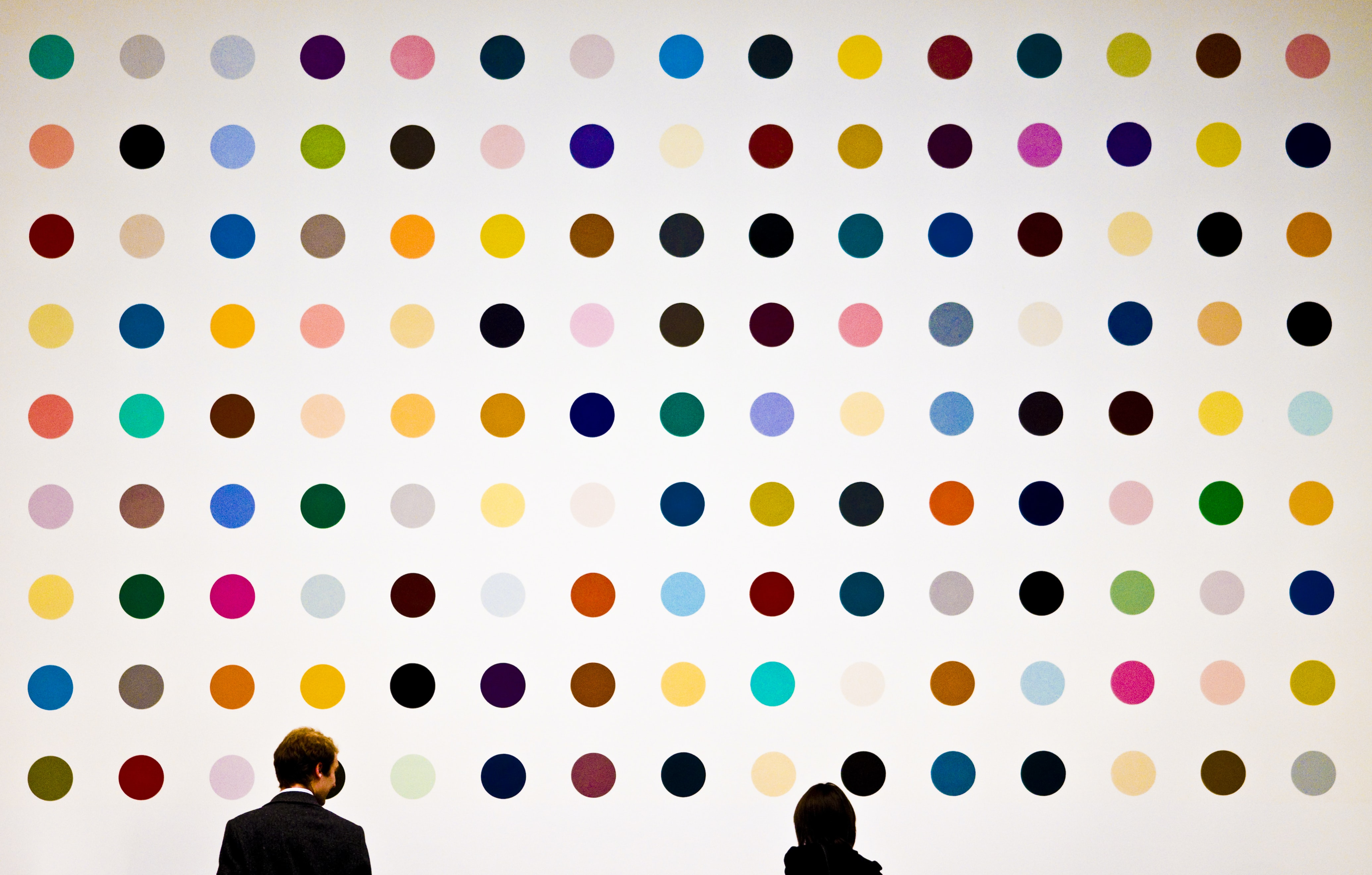 man and woman facing wall painted with multicolored polka dots