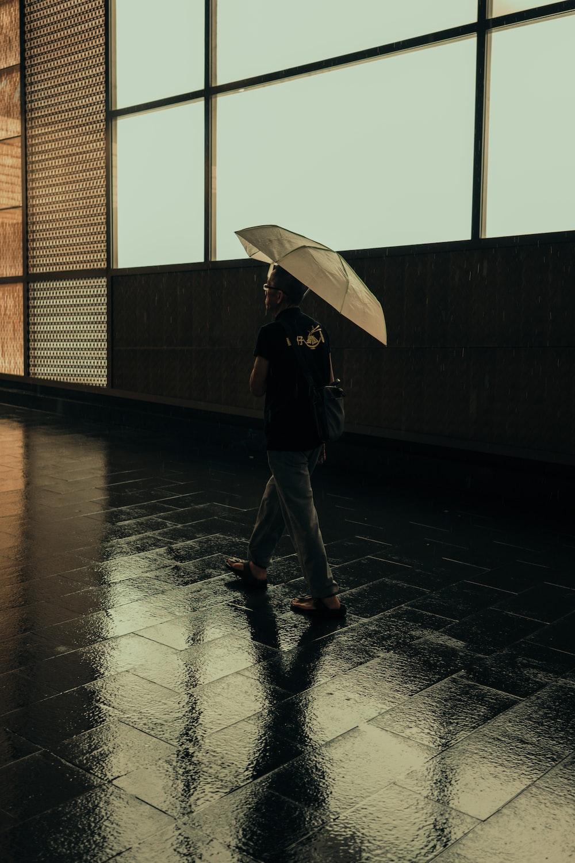 man walking while holding umbrella