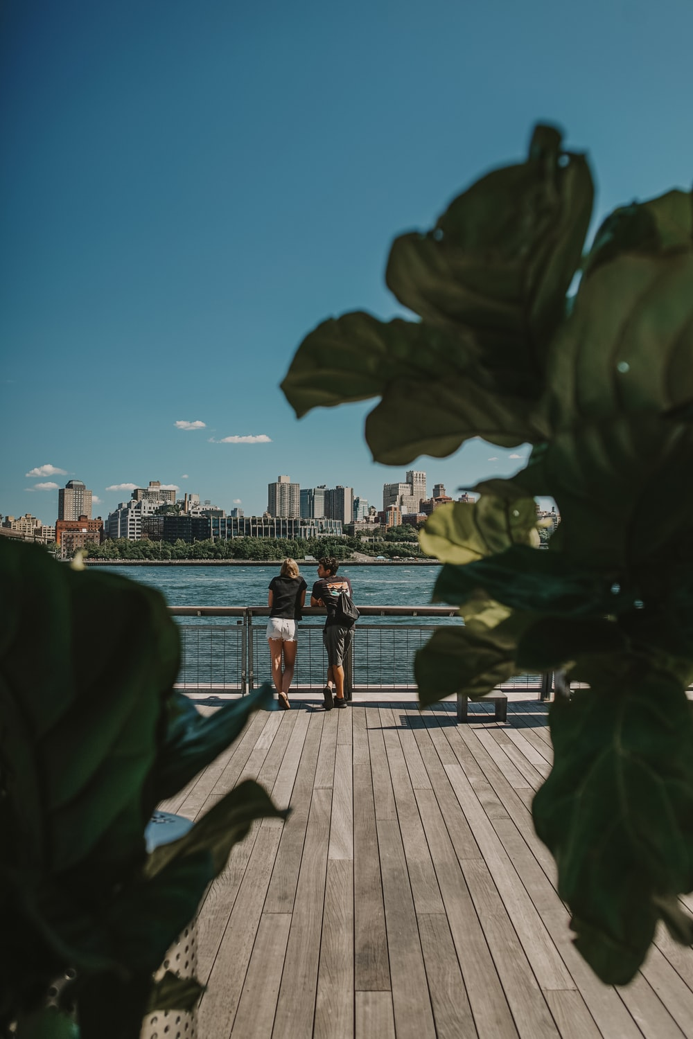 couple standing near railings and body of water
