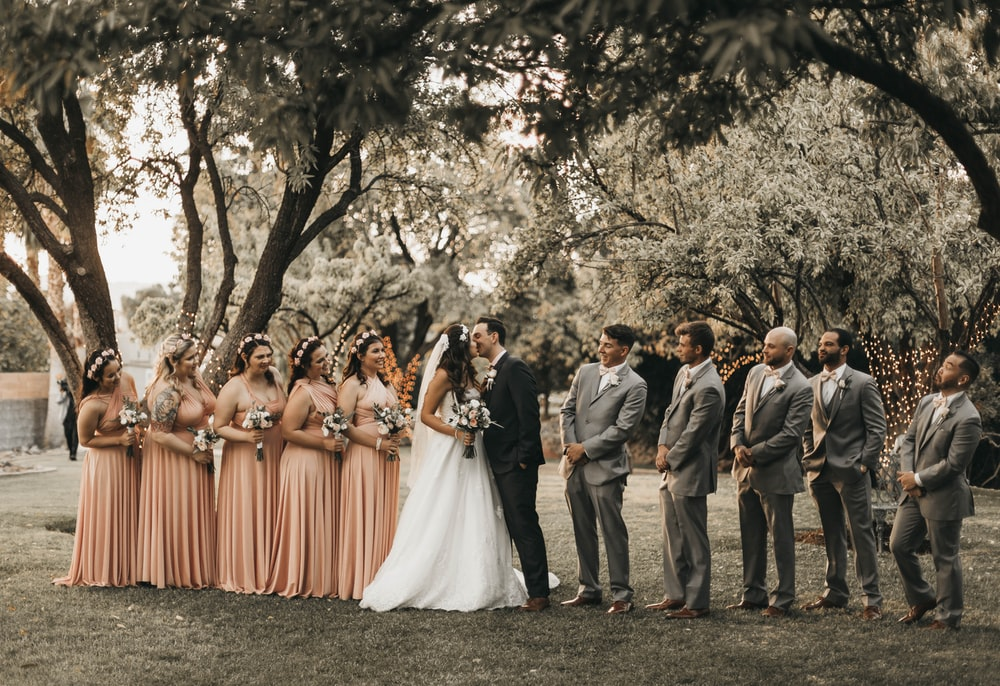 5 groomsmen and 5 brides maid standing next to the couple kissing