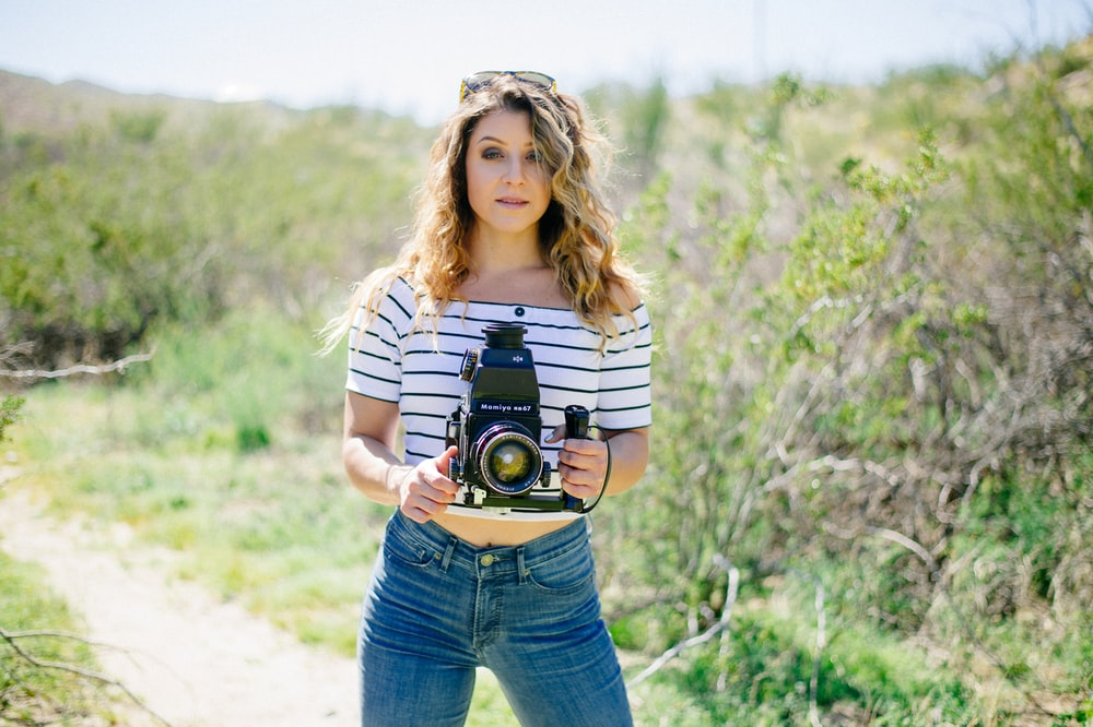 woman holding camera standing near green tall grass during daytime