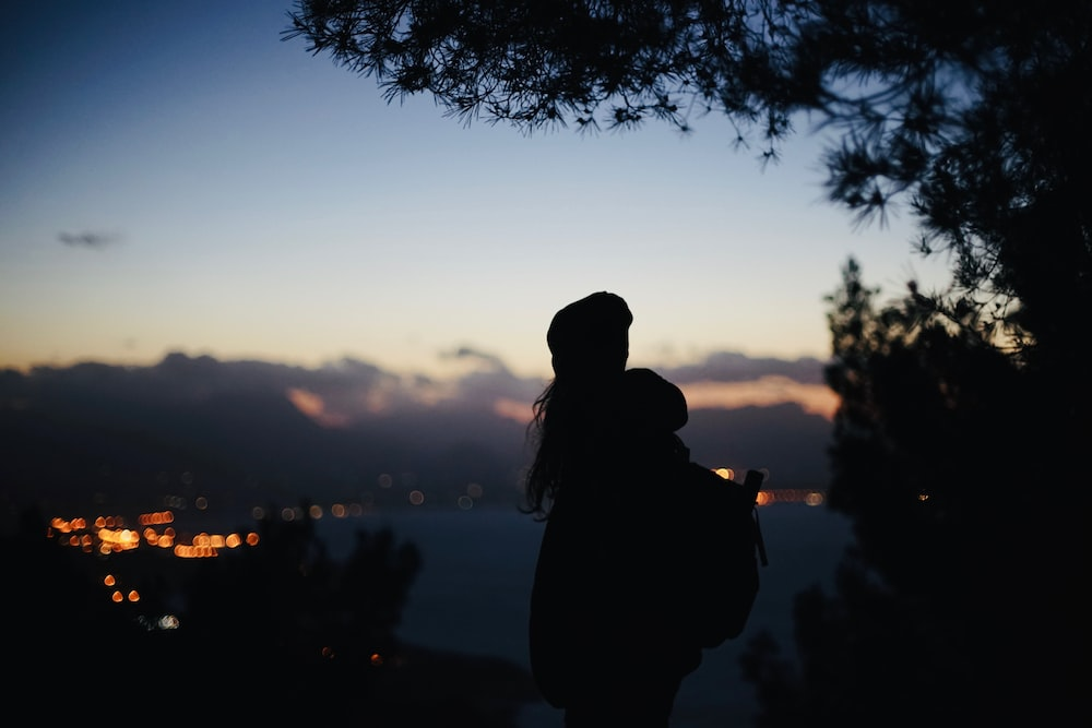 silhouette view of woman carrying backpack