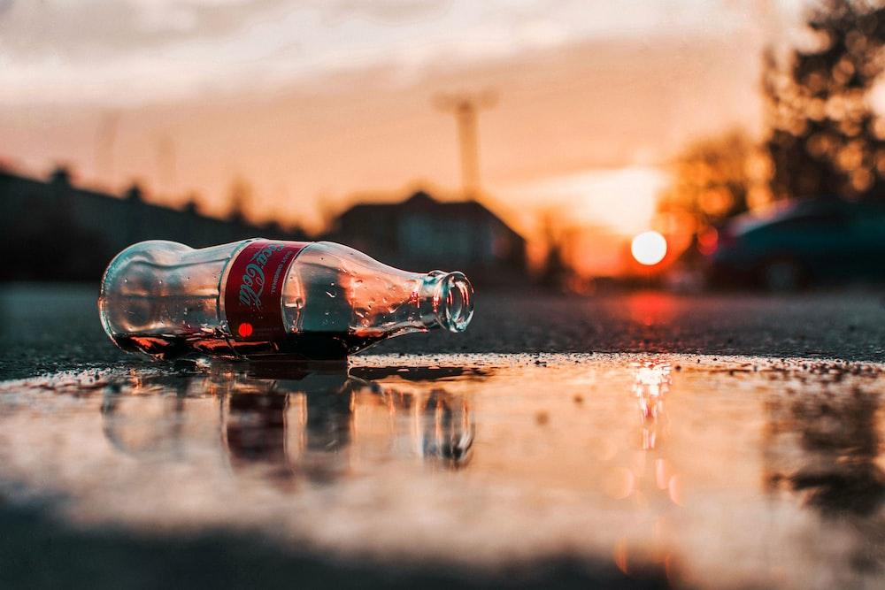 coca-cola bottle on grey pavement