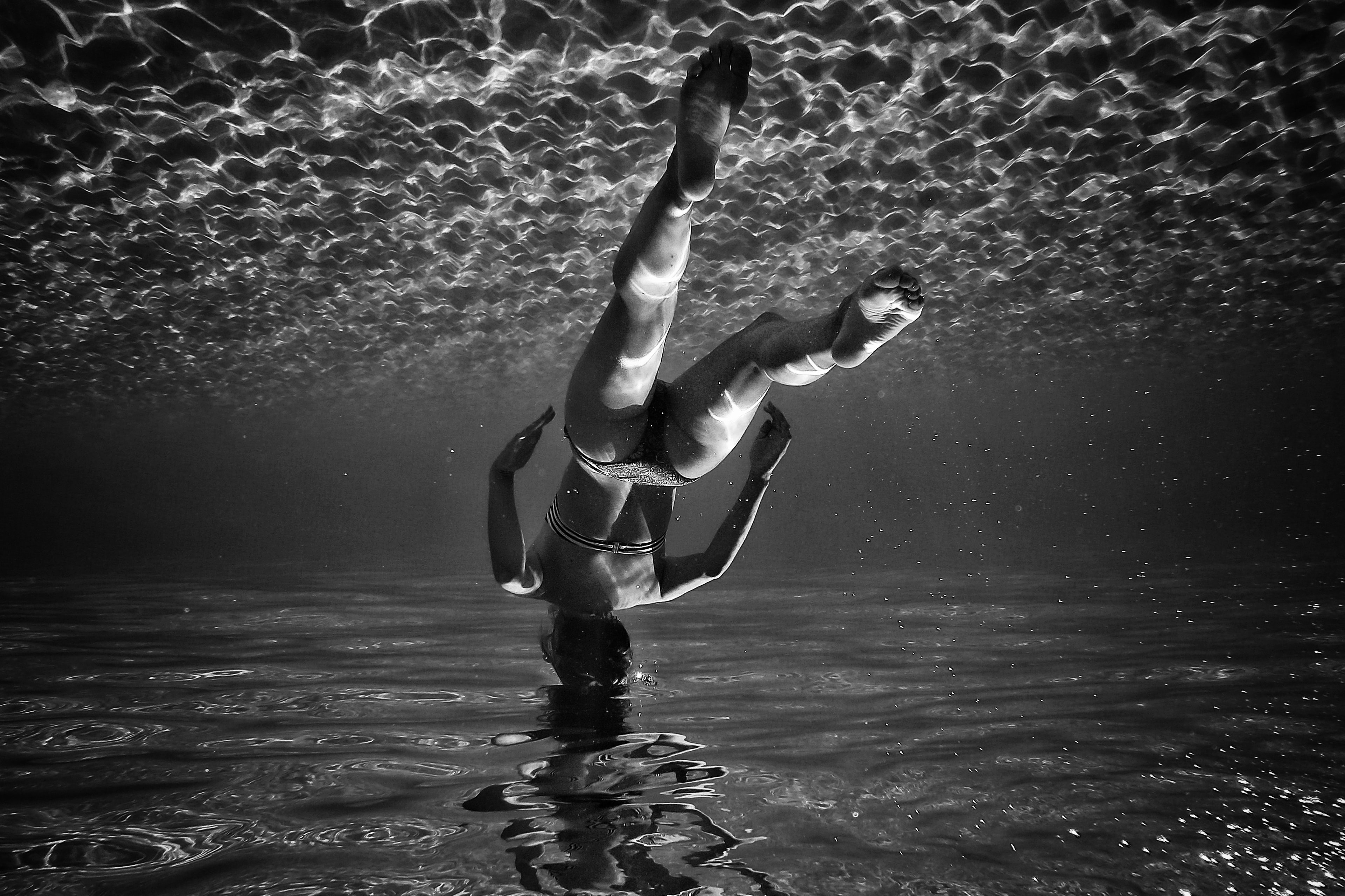 grayscale photo of woman swimming